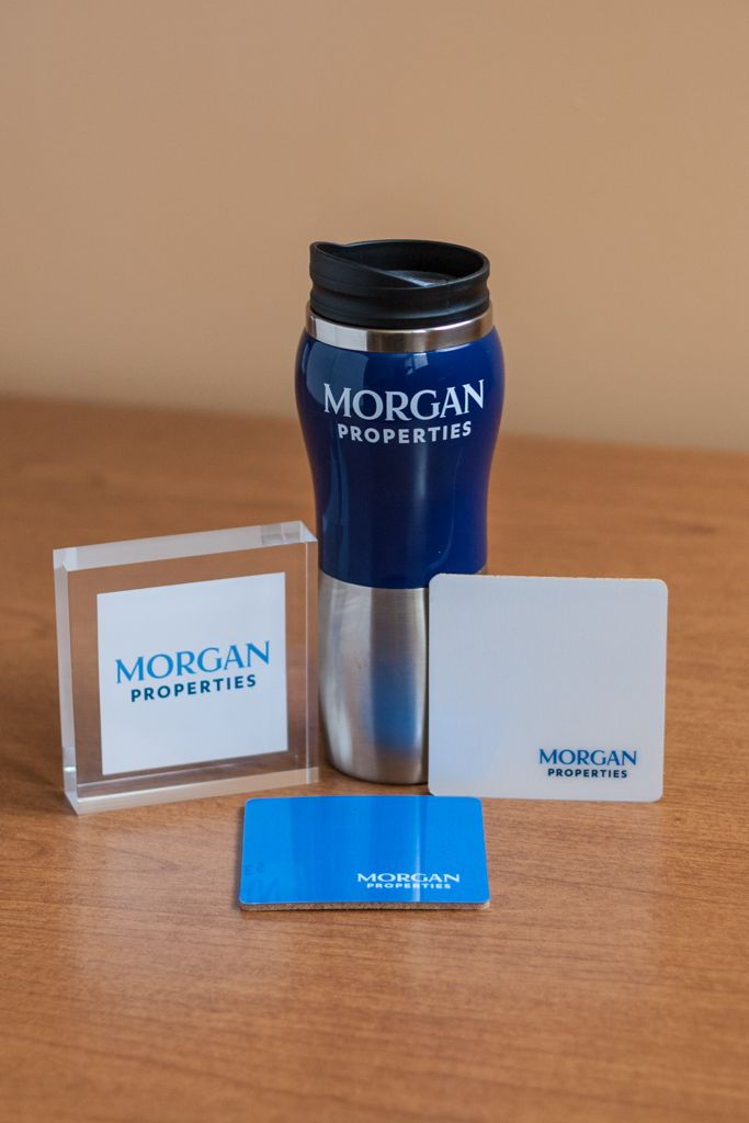 Morgan Properties branded travel thermos, drink coaster, and glass sign